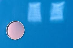 Fensterreflexion-an-blauer-Hauswand